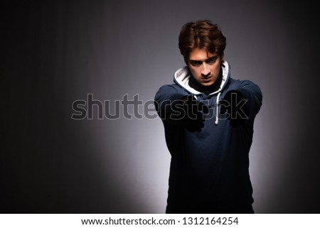 Young gangster in hood on grey background #1312164254