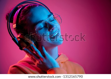 Fashion pretty woman with headphones listening to music over red neon background at studio. #1312165790