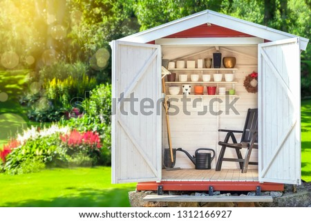 Garden shed filled with gardening tools. Shovels, rake, pots, water pitcher in storage hut. Green sunny garden in the background. #1312166927