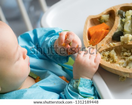 Baby eating by hands, Baby eating organic bio vegetables with BLW method, baby led weaning. Happy vegetarian kid eating lunch. Toddler eat himself, self-feeding. infant baby eating.  #1312189448