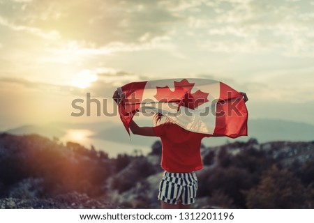 Happy child teenage girl waving the flag of Canada while running at sunset #1312201196