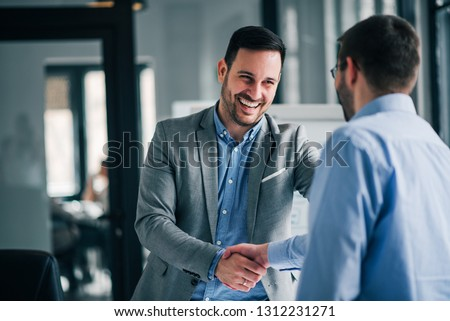 Portrait of cheerful young manager handshake with new employee.  Royalty-Free Stock Photo #1312231271