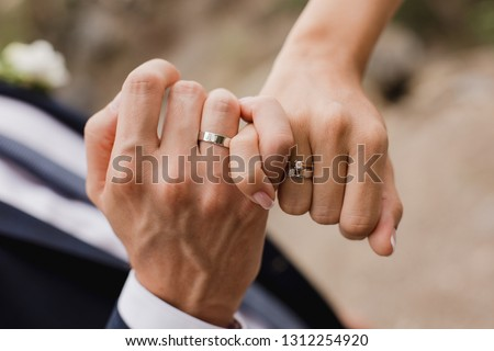 Picture of man and woman with wedding ring.Young married couple holding hands, ceremony wedding day. Newly wed couple's hands with wedding rings.  #1312254920