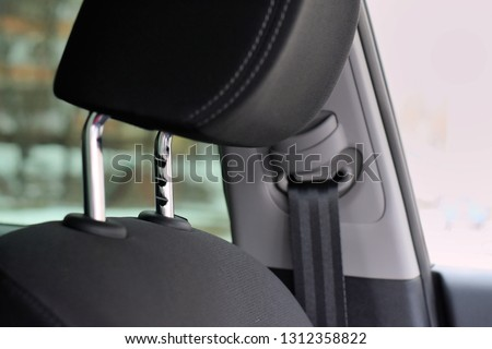 Black car headrest with selective focus and metal protect element. Blurred automobile safe passenger seat belt on background. Comfortable car headrests with shiny chrome height adjustment  Royalty-Free Stock Photo #1312358822