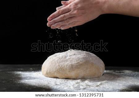 Female hands sprinkling flour over fresh dough on dark background. #1312395731