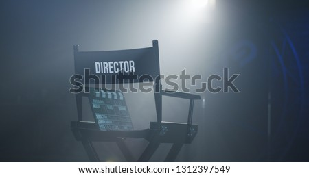 Empty black chair with sign Director and clapperboard in spotlight on filming set Royalty-Free Stock Photo #1312397549