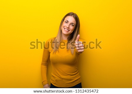 Young woman on yellow background giving a thumbs up gesture because something good has happened #1312435472