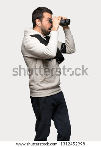 Sport man and looking in the distance with binoculars over isolated grey background #1312452998