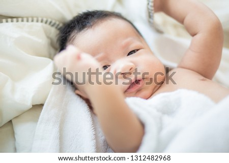 Funny infant baby boy lying on bed after wake up in morning #1312482968