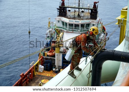 An abseiler wearing Personal Protective Equipment (PPE) standing on pipeline for painting activities with background marine vessel floating at the sea. Royalty-Free Stock Photo #1312507694