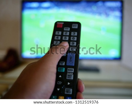 closeup of hand with the remote control television and presses the button.  #1312519376