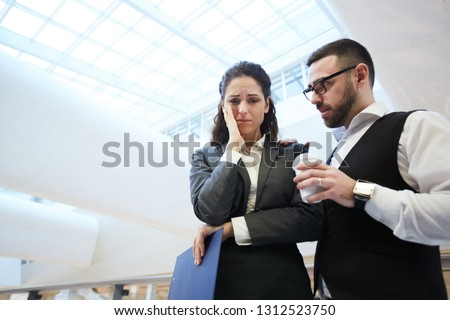 Very upset secretary or broker in formalwear crying while colleague offering her drink and help #1312523750