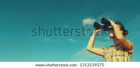 Young scout girl looks through binoculars on blue sky background Royalty-Free Stock Photo #1312539275