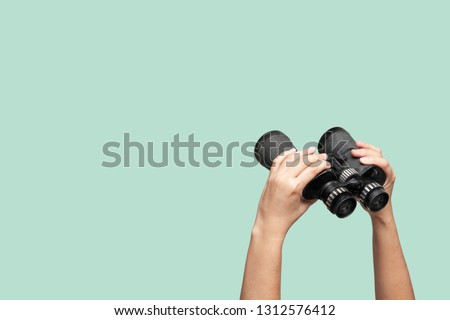 Hands holding binoculars on green background, looking through binoculars, journey, find and search concept. Royalty-Free Stock Photo #1312576412