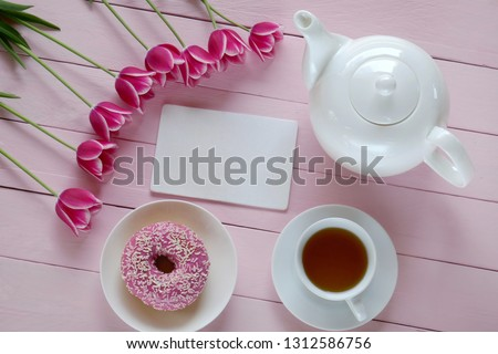 Spring tea.Flat lay.Spring to-do list.pink tulips flowers, white teapot, blank notebook, cup of tea on a pink wooden background.top view, copy space.Spring mood #1312586756