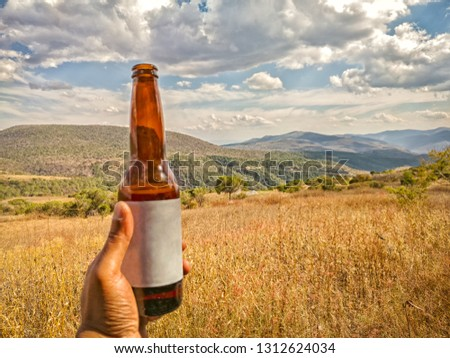 A hand is holding a glass beer bottle with a blank label. A sunny day outdoors with mountains in the background. Travel in rural Guerrero Mexico. #1312624034