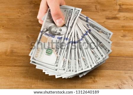 hand, money dollars usa - Image on wooden background