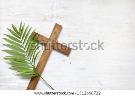 Cross and palm on wooden white background easter sign symbol concept #1312668722