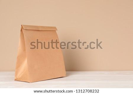 Paper bag on table against color background. Mockup for design #1312708232