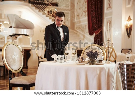 Everything must be perfect. Process of preparing place for special visitors. Waiter in classical wear works on the servering. #1312877003
