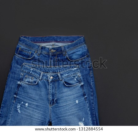 Set of men's and women's blue jeans on black background top view flat lay. Detail of nice blue jeans. Jeans texture or denim background. Trend clothing. Beauty and fashion, clothing concept.  #1312884554