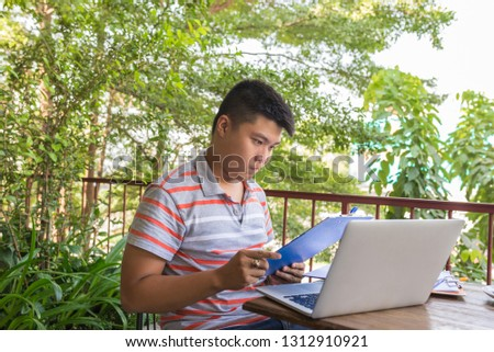 Young Asian freelancer reading financial document and report #1312910921