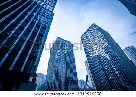Bottom view of modern skyscrapers in business district against blue sky #1312916558
