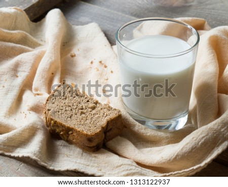 a glass of milk and a slice of rye bread for breakfast #1313122937