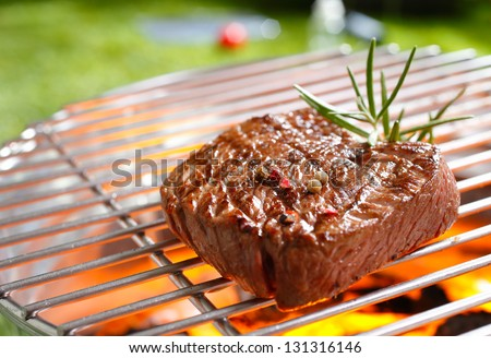 A thick strip steak being grilled outdoors #131316146