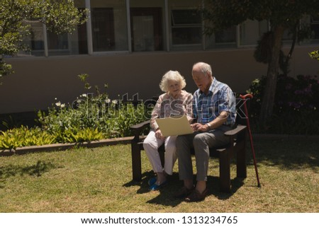 Front view of happy senior couple using laptop and sitting on bench in garden #1313234765