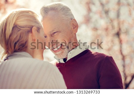 My treasure. Handsome gray-haired man expressing positivity while looking at his woman #1313269733