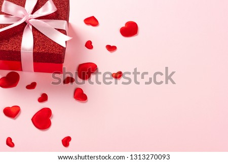 Red gift box with pink ribbon and scattered red hearts on pink background. Christmas, Valentine's day or birthday concept. Place for text. #1313270093