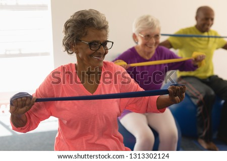 Front view of happy diverse senior woman exercising with resistance band in fitness studio Royalty-Free Stock Photo #1313302124