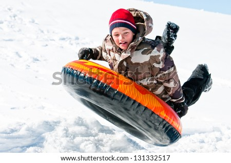 A happy boy up in the air on a tube sledding in the snow.
