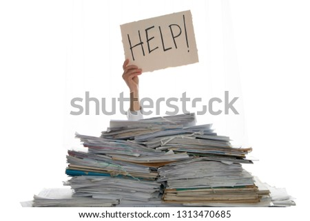 Person under a pile of papers with a hand holding a sign of help. Accounting. Royalty-Free Stock Photo #1313470685