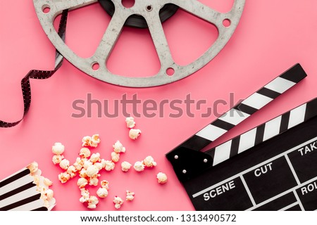 Movie premiere concept. Clapperboard, film stock, popcorn on pink background top view