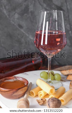 Glass of tasty wine with snacks on table #1313512220