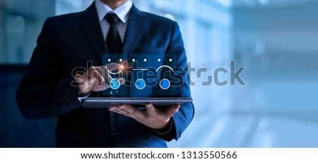 Businessman touching and drawing face emoticon smile on the tablet, service mind. blue background. Customer service concept. Royalty-Free Stock Photo #1313550566