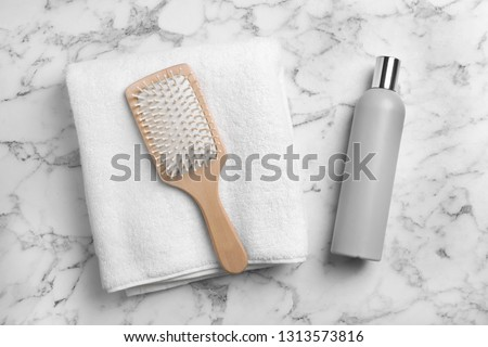 Towel, hair brush and shampoo on marble background, top view Royalty-Free Stock Photo #1313573816