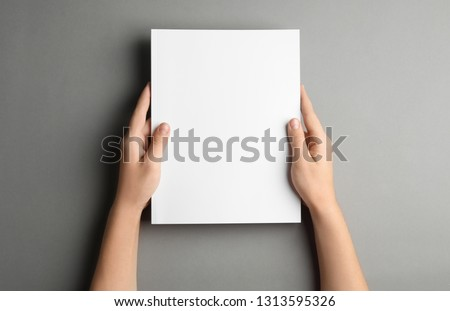 Woman holding brochure with blank cover on grey background, top view. Mock up for design #1313595326
