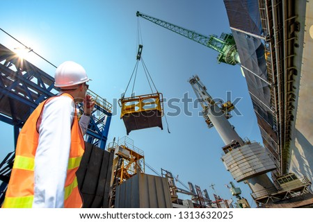 engineering, loading master connecting with gantry crane driver by walkie talkie for lifting safety operation in loading the goods or shipment #1313632025