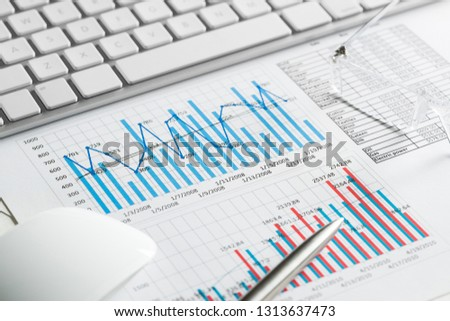 Business workplace with keyboard mouse and papers with graphs and diagrams #1313637473