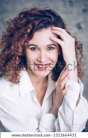 Young woman with brunette curly hair, fashionable toning. #1313664431