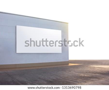 Blank Billboard on white wall of building in warm evening dusk.