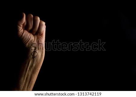 Female hand in fist raised up on a dark background close up #1313742119
