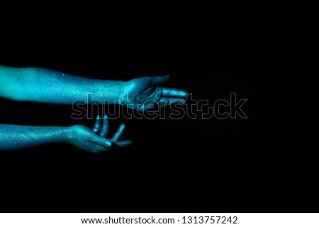 Painted female hands on dark background Royalty-Free Stock Photo #1313757242