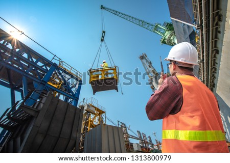 engineering, loading master connecting to gantry crane driver by walkie talkie for lifting safety in loading the goods or shipment, lifting by gantry crane, working at risk on the high level insurance #1313800979