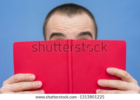 Man reads the book, visible only eyebrows, facial expressions, close up, background, copy space, for advertising, slogan, front view
