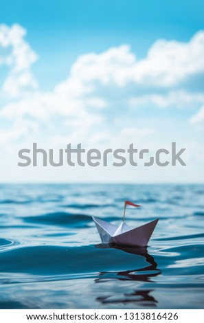 Paper Boat with Flag on the Ocean #1313816426