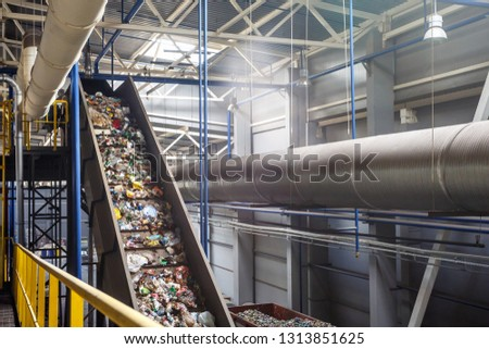 MINSK, BELARUS - MAY 2018: moving conveyor transporter on Modern waste recycling processing plant. Separate and sorting garbage collection. Recycling and storage of waste for further disposal.  #1313851625